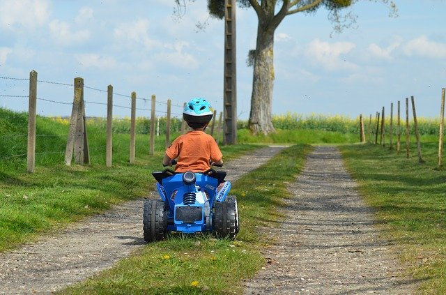 kind auf Quad mit fahrrad helm